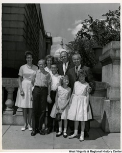 Congressman Arch A. Moore, Jr. with an unidentified family of seven. The Capitol dome can be seen in the background.