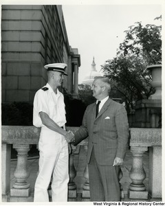 Congressman Arch A. Moore, Jr. shaking the hand of a man in a Navy uniform.  The Capitol Building can be seen in the background.