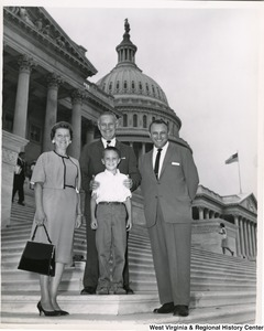 Congressman Arch A. Moore, Jr. standing on the steps of the capitol with an unidentified family of three.