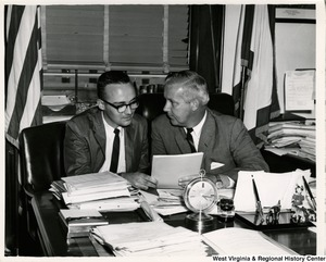Congressman Arch A. Moore, Jr. sitting at his desk showing an unidentified man a document.