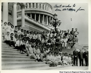 "Congressman Arch A. Moore, Jr. with a large unidentified group on the steps of the Capitol Building.  The photo is signed, but the writing is smudged. It reads, ""Best wishes to Don ???? from"""
