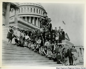 Congressman Arch A. Moore, Jr. with his wife Shelley and a large unidentified group on the steps of the Capitol Building.