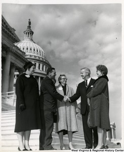 Congressman Arch A. Moore, Jr. shaking hands with an unidentified man. Three unidentified women are standing with them watching.