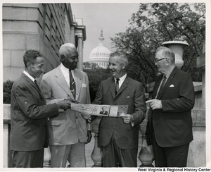 "Congressman Arch A. Moore, Jr. showing a pamphlet ""The Capital Guide"" to three unidentified men."