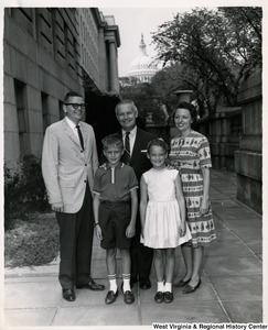 Congressman Arch A. Moore standing with an unidentified family of four.
