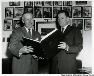 Congressman Arch A. Moore, Jr. looking at a book with an unidentified man.