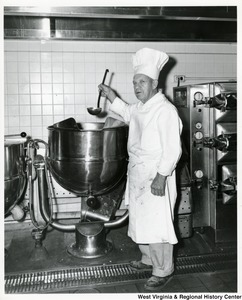 An unidentified chef in front of a large pot.