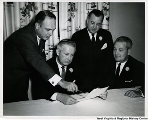 Congressman Arch A. Moore, Jr. reviewing a document with three unidentified men, presumably Weirton Steel Co. employees.