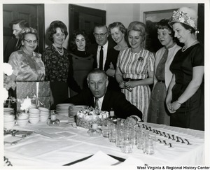 Congressman Arch A. Moore, Jr. blowing out candles on his birthday cake. His wife, Sadie (Shelley), is the first person standing on the right.
