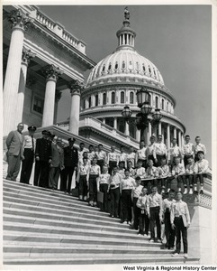 Congressman Arch A. Moore, Jr. standing on the steps of the Capitol with an unidentified group of boys. The boys are wearing uniforms with sashes and badges.