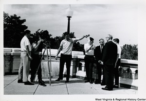 A unidentified group is filming Congressman Moore and three other unidentified men. A man is holding up a film clapperboard in front of the camera.