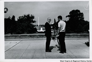 Two unidentified men talking. It may relate to Boys Nation. A camera is set up in front of them and appears to be pointed at the Washington Monument.