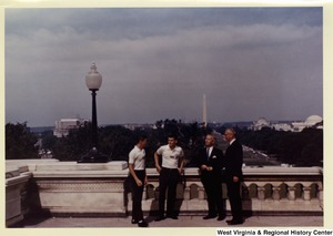 Congressman Arch A. Moore, Jr. and an unidentified man talking to two members of the American Legion Boys Nation. The Washington Monument can be seen in the background.