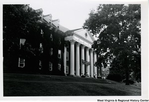 "An unidentified building with a banner stating, ""Boys Nation, The American Legion"" strung across the front pillars. A group of boys are sitting on the steps in front of the building."