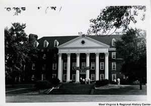"A building with a banner stating, ""Boys Nation The American Legion."" A group of young men are sitting or standing on the steps."