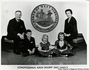 Congressman Arch A. Moore, Jr. with his wife and three children. The seal of West Virginia in the background.