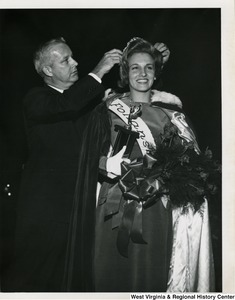 "Congressman Arch A. Moore, Jr. placing a tiara on the head of an unidentified pageant contestant. She appears to be wearing a sash that reads, ""Follansbee."""