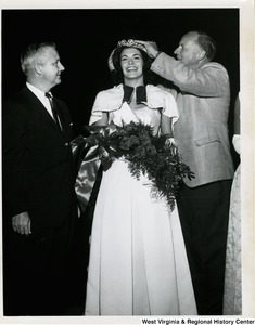 Congressman Arch A. Moore, Jr. watching an unidentified man place a crown on a pageant contestant's head.