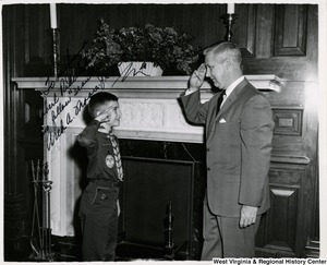 "Congressman Arch A. Moore, Jr. saluting Cub Scout Robert (Bobby) Riddle, II in the Sam Rayburn Reception Room. Riddle presented Moore with a Boy Scout emblem to celebrate the 54th anniversary of the Boy Scouts of America to wear during Scout Week (February 7-13). The photograph is signed: "" To my friend Robert Riddle from his fellow 'scouters.' Arch A. Moore, Jr. M.C."""