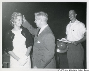 Congressman Arch A. Moore, Jr. placing a tiara on the head of an unidentified woman. An unidentified man is standing behind Moore watching.