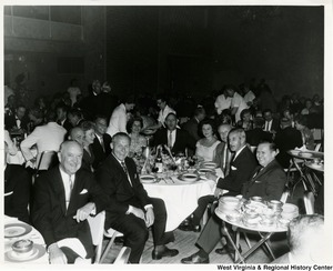 Congressman Arch A. Moore, Jr. sitting beside his wife, Shelley, at a large event.
