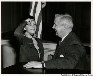 Congressman Arch A. Moore, Jr. being saluted by a unidentified Cub Scout.