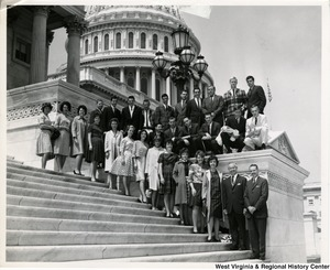 Congressman Arch A. Moore, Jr. standing on the steps of the Capitol with an unidentified group of people.