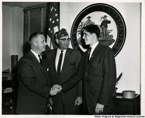 Congressman Arch A. Moore, Jr. shaking hands with Lewis Brewer. Jim Fawcett, member of Veterans of Foreign Wars 3081, is standing beside them.