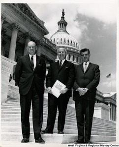 Congressman Arch A. Moore, Jr. standing on the steps of the Capitol with two unidentified men.