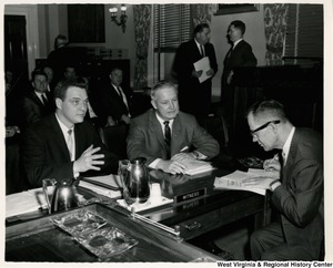 Congressman Arch A. Moore, Jr. having a conversation with two unidentified men.