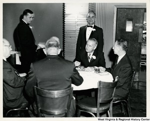 Congressman Arch A. Moore, Jr. sitting at a table with four unidentified men having a conversation during the Elks Memorial Service.