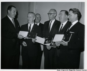 Congressman Arch A. Moore, Jr. holding a plaque and standing with members of the West Virginia delegation. From right to left: Senators Robert C. Byrd,  Jennings Randolph, Congressmen Ken Hechler, unknown, Arch A. Moore Jr., unknown.