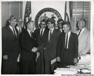 Congressman Arch A. Moore, Jr. shaking hands with the Post Commander for Keyser (W.Va.) Veterans of Foreign Wars Post. Four other West Virginia VFW are standing with them, along with two others.