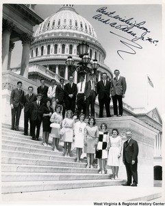 "Congressman Arch A. Moore, Jr. standing on the steps of the Capitol with an unidentified group of people. The photograph is signed "" Best wishes from Arch A. Moore, Jr. M.C."""