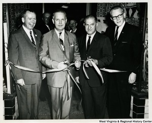 Congressman Arch A. Moore, Jr. getting ready to cut a ribbon at a re-election campaign event. Three other unidentified men are standing beside him.