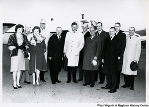 Congressman Arch A. Moore, Jr. (left of center) with a small group of people in front of a plane. His wife, Shelley, is the first person on the left, front.