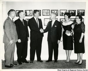 Congressman Arch A. Moore, Jr. shaking hands with an unidentified man. Shelley Moore is standing beside Arch. Three other people are standing with them.