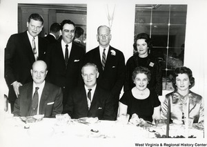 Congressman Arch A. Moore, Jr. seated at a table with his wife, Shelley, and two unidentified people. Standing behind them are Congressman John M. Slack, Jr., Cecil Underwood, his wife Hovah, and another unidentified man.