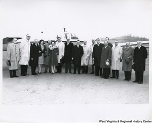 Congressman Arch A. Moore, Jr. standing beside his wife Shelley, with an unidentified group of people in front of a airplane.