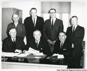 Congressman Arch A. Moore, Jr. (seated, center) with six unidentified men.