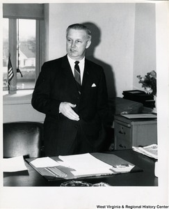 Congressman Arch A. Moore, Jr. standing behind his desk.