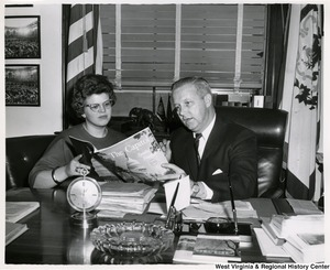 "Congressman Arch A. Moore, Jr. sitting at his desk showing the magazine ""The Capitol"" to an unidentified woman."