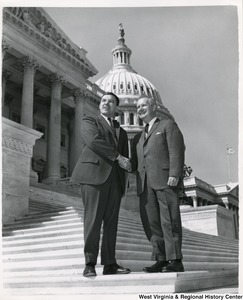 Congressman Arch A. Moore, Jr. shaking hands with an unidentified man. They are standing on the steps of the Capitol.