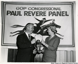 Congressman Arch A. Moore, Jr. holding a lantern with an unidentified woman. A banner behind them reads 'GOP Congressional Paul Revere Panel.""