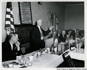 Congressman Arch A. Moore, Jr. seated at a table with other unidentified men listening to an unidentified man from Weirton Steel speak.