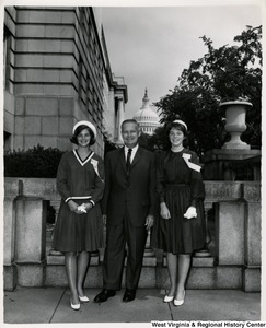 Congressman Arch A. Moore, Jr. standing with two unidentified young women. The Capitol building can be seen in the background.