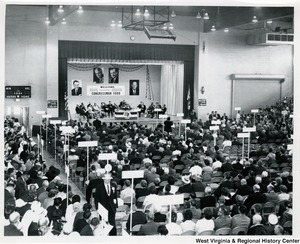 Congressman Arch A. Moore, Jr. on stage speaking to a audience at a Republican (GOP) party event for 1964. A banner on the wall behind him reads 'Welcome Cecil - Cooper, Congressman Ford.'  A group of people are sitting on the stage behind him.