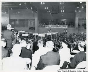 "The audience, separated by counties, during the GOP (Republican) rally of 1964. The photograph was taken from behind the people sitting on the stage. An unidentified man is speaking to the audience.  In the background, a banner reads ""Welcome Home Governor Underwood."""