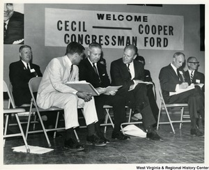 "Congressman Arch A. Moore, Jr. sitting between Congressman Gerald Ford and an unidentified man. Moore is looking at some papers, while Congressman Ford is talking to them.  In the background a banner reads "" Welcome Cecil - Cooper, Congressman Ford."""