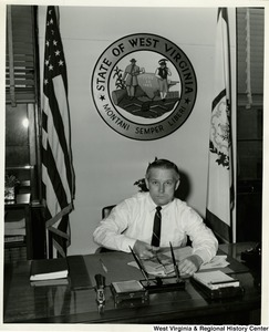 Congressman Arch A. Moore, Jr. sitting at his desk cutting out a newspaper article.
